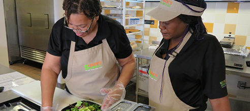 Barbara and a Sobik's Subs Cafe employee help to create a sandwich for an Orlando customer