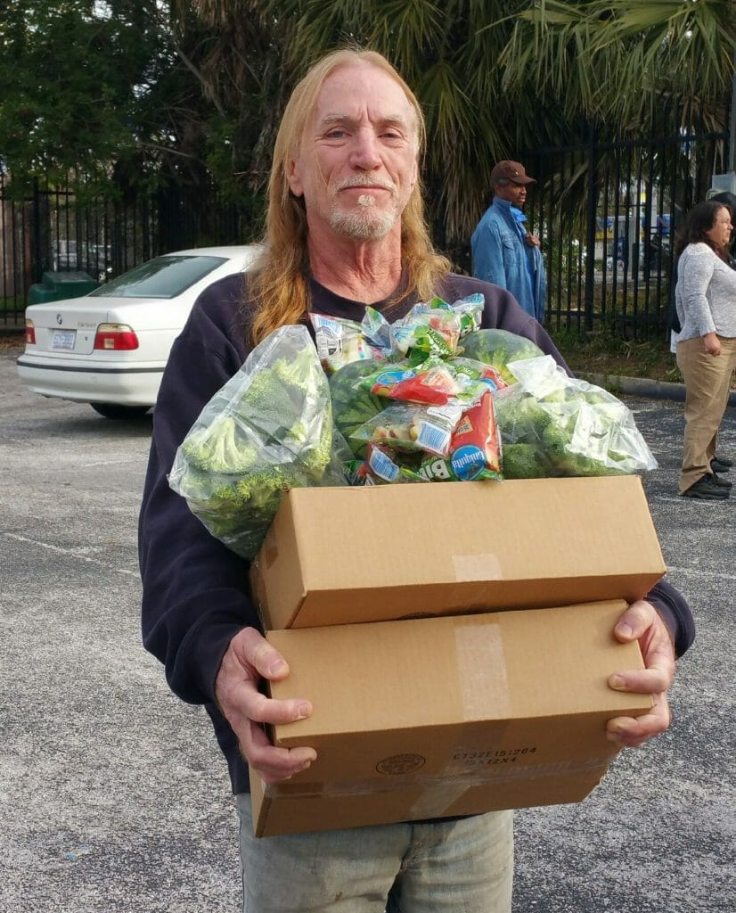 A resident of Pathlight HOME picks up a box of food donated by Second Harvest Food Bank and Universal Orlando Foundation