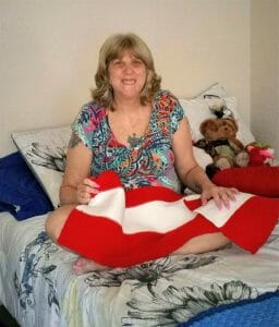 Jennifer, a resident of the Pathlight HOME affordable efficiency apartments, with the blanket she knitted for her son