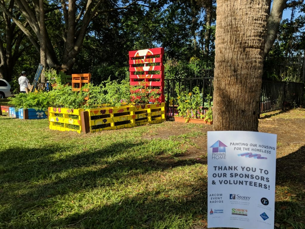 Sponsor signage thanks Orlando volunteers and supporters of Pathlight HOME's volunteer painting day at Maxwell Garden