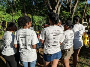 Student volunteers show off the back of their t-shirts while volunteering at Pathlight HOME's Housing for the Homeless