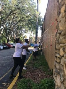 Volunteers paint the exterior of Maxwell Garden, a renovated motel that is now affordable permanent supportive housing apartments for former homeless in Orlando